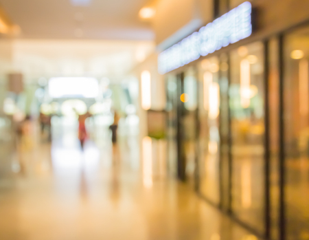 blurred people walking on corridor in department store with shop