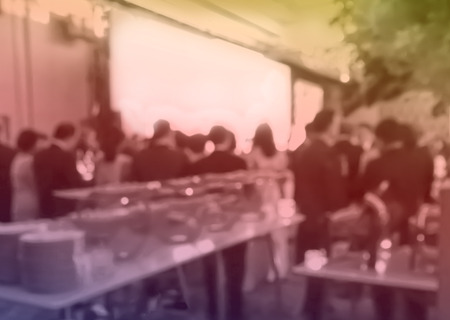 blurred people eating and talking in hotel ballroom