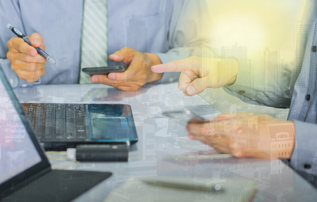 successed businessman working with smart phone digital tablet laptop computer in office with double exposure building  filter effect Stock Photo
