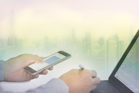 hand of  businessman working with smart phone digital tabletwith building background Stock Photo
