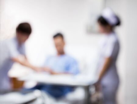 blurred nurse and doctor visit patient on bed