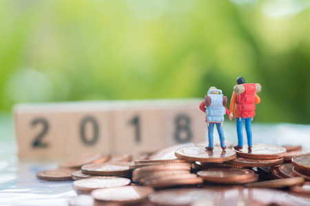 Miniature backpackers on the stack of coins are turning their back towards and looking forward to wooden numbers 2018, travel and business concept.