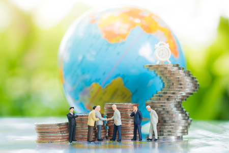 Miniature businessman handshaking with globe and growing stacks of coins background using as commitment, agreement, investment and partnership business concept.
