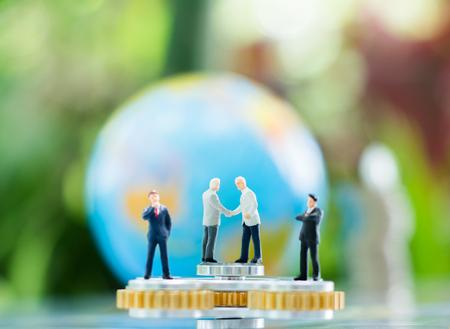 Miniatuur zakenmanhandenschudden op de fidgetspinner met vage bol en stapel muntstukken die als achtergrondverloving, overeenkomst, investerings en vennootschapconcept gebruiken.