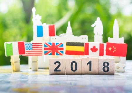 A wooden number 2018 with internation flags background on a world map using as happy new year 2018 concept, international cooperation,teamwork and partnership business concept.