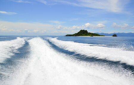 Wake caused by cruise ship or trace tails of speed boat on water surface in the ocean using as natural background.