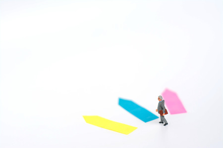 Three direction arrow choices, left, right or move forward, miniature model figure of businessman are taking decisions for the future, choice way.