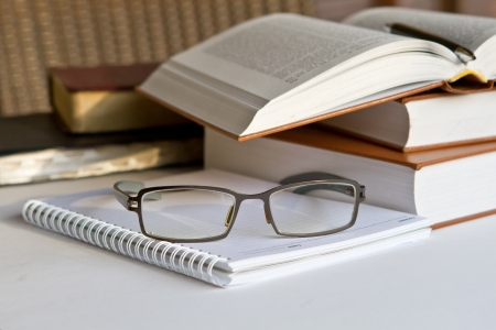 Stack of books with notepad and glasses Stock Photo