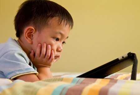 Chinese boy using tablet while lying on bed photo
