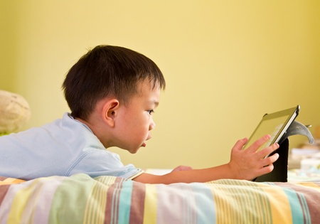 parental control: Chinese boy using tablet while lying on bed Stock Photo