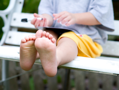 Beautiful toddlers feet sitting on a bench photo