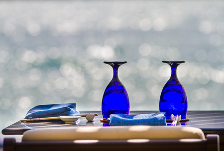 dinner cruise: Blue glasses and cutlery on sea background Stock Photo