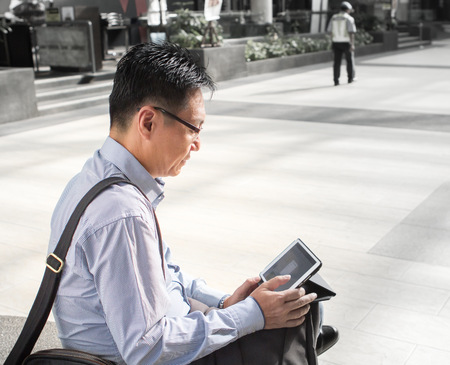 Asian businessman on tablet computer photo