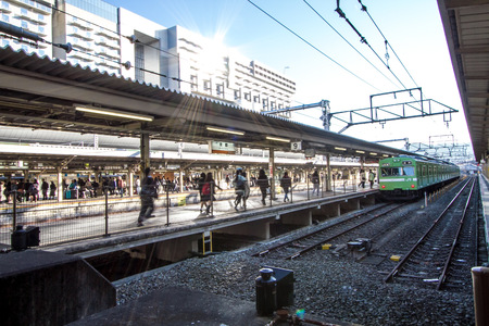 existed: E-KYOTO, JAPAN - Nov 2015: Travelers hurry at Kyoto Station in Kyoto, Japan. It is Japans 2nd biggest train station building. The building is recent, but station existed here since 1877.