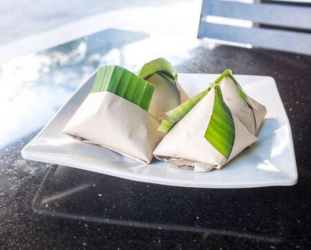 lemak: Wrapped nasi lemak on white plate Stock Photo