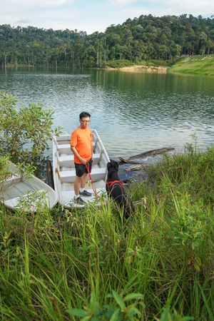 Man and dog spending time beside a lake Stock Photo