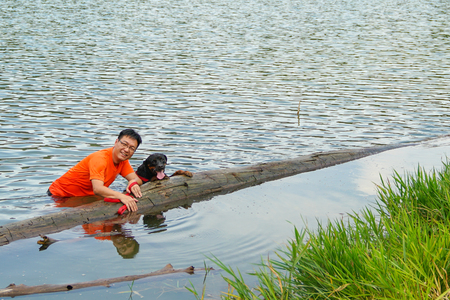 Man and dog having fun in the lake