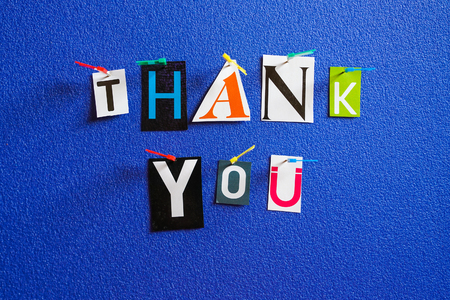 Thank you words in various colors pinned on blue board