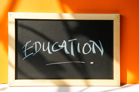 Black board on orange background with text Education written in chalk Stock Photo