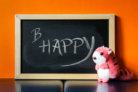 Black board with text B Happy written on chalk and a pink soft toy next to it