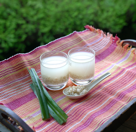 Barley water or soup in glasses and cooked pearly barley on spoon with pandan leaves 版權商用圖片