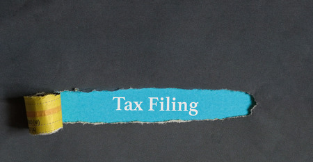 File tax return reminder : words on a torn hole as alert