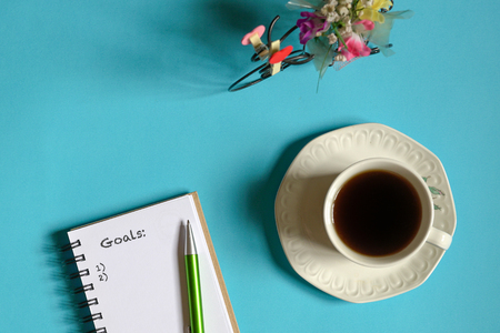 Top view goals list with memo pad, cup of coffee and pen on pastel blue background Stok Fotoğraf