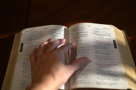 Hand on open bible with Psalm 27 in focus