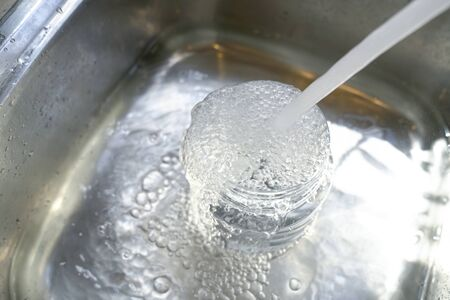 Water from tap into plastic container and it overflow to the sink. Save water concept. 版權商用圖片
