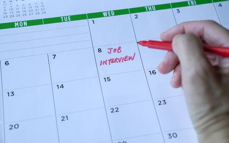 Job interview words written on table calendar with red marker. Employment or career concept.