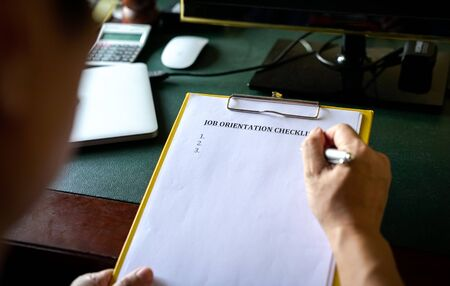Manager going through job orientation checklist. An on boarding concept. Closeup view. Archivio Fotografico