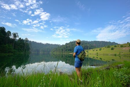 Hiker cum photographer facing a beautiful lake with forest landscape at the background.
