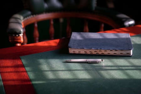 Closed bible on the edge of table with chesterfield chair at the background. Light play forming lines and patterns on surface. 写真素材
