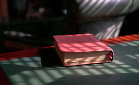 Holy bible on top of red wood and green leather table. Light play forming lines patterns and shadows. 写真素材