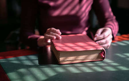 Woman's hands on a closed bible on a table. Artistic lines patterns of light and shadow.