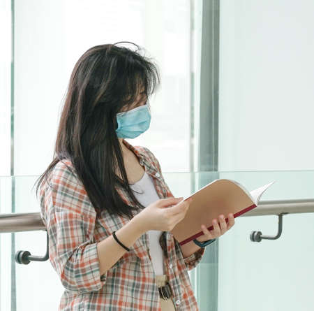 Asian woman wearing face mask reading a book Stock Photo