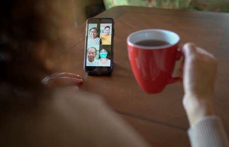 Woman with a cup of coffee having a group videocall and chat over her mobile phone at home