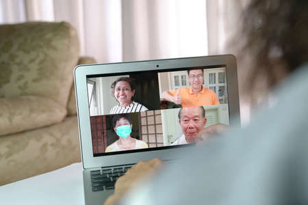 Woman having video call and chat with friends via computer laptop in her house living hall