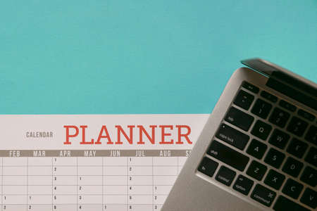Computer laptop on top of calendar planner and blue tabletop. Business planning concept.
