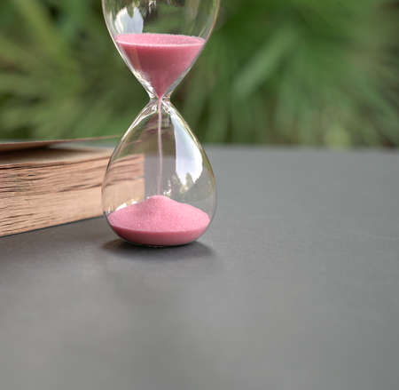 Hour glass with sand flowing, next to a book. Close up. Time management concept.