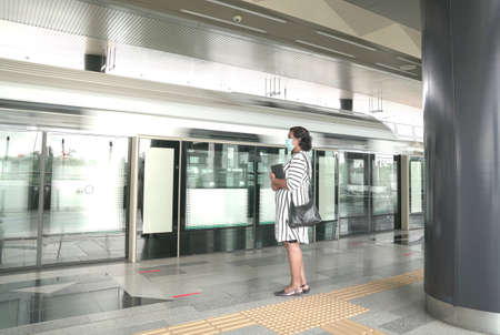 Woman wearing face mask on waiting for train at the platform of a subway station.