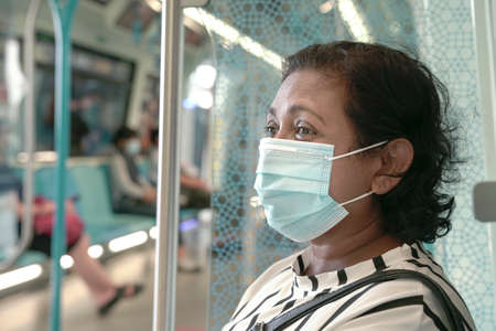 Woman commuter wearing face mask inside train. Travel during pandemic concept. 版權商用圖片