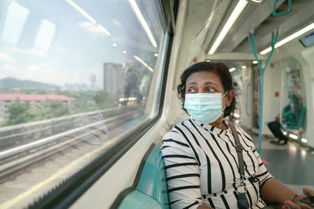 Woman commuter wearing face mask inside subway train. Travel new normal during pandemic. 版權商用圖片