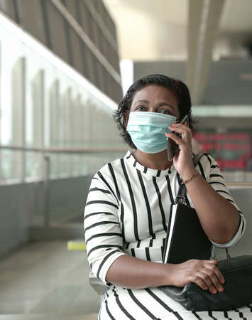 Portrait of woman wearing face mask sitting and talking on the cellphone. Copy space.
