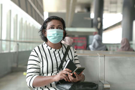 Woman wearing face mask sitting and waiting at subway station, commuters at the background 版權商用圖片