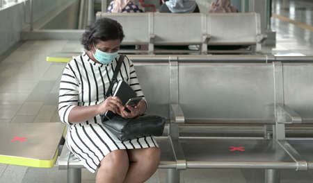 Woman wearing face mask sitting and reading her cellphone at subway station, commuters at the background.