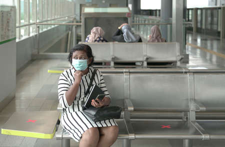Woman wearing face mask sitting at subway station waiting for train with other commuters at the background 版權商用圖片