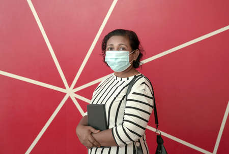 Portrait of businesswoman wearing face mask, holding a diary. Red background.
