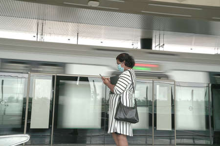 Woman wearing face mask reading cellphone, waiting for train at the platform of a subway station.