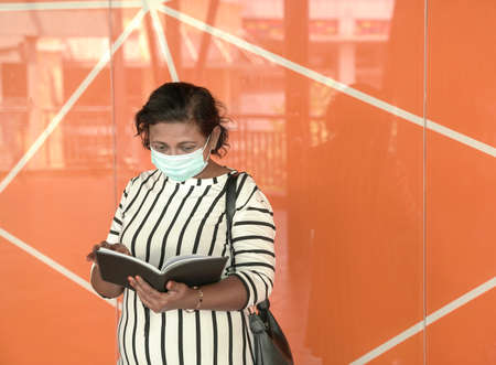 Portrait of businesswoman wearing face mask, looking at her diary. Orange background. 版權商用圖片